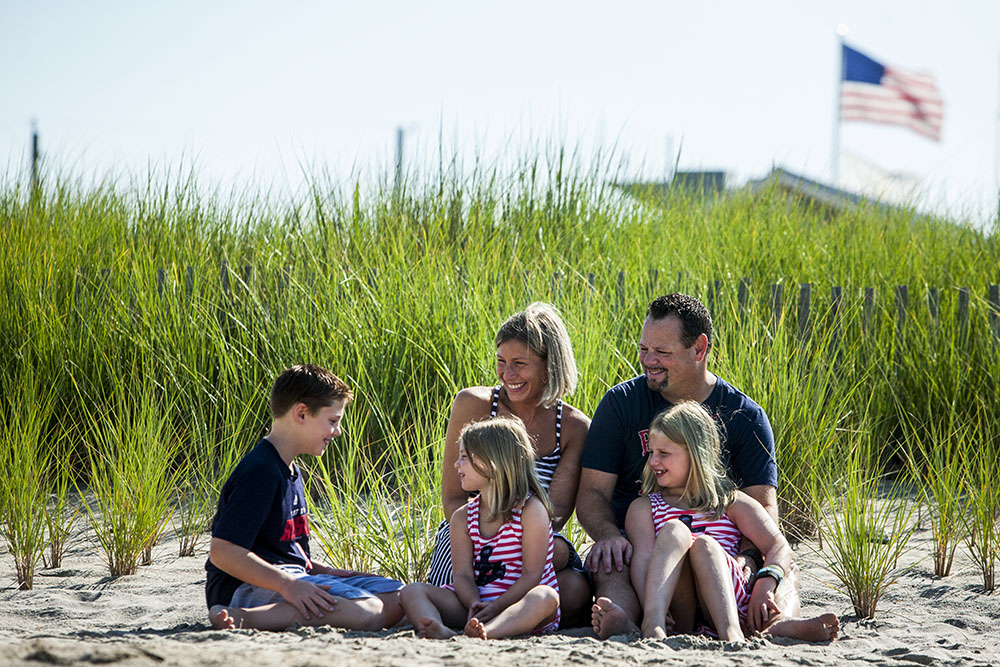 Candid family portrait on a Rhode Island beach with grass, sand and an american flag.