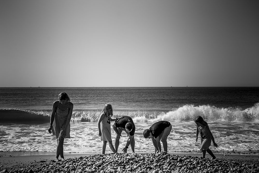 Candid beach portrait of family looking through a pile of rocks with a wave breaking behind them, the picture is in black and white and the beach is in Rhode Island.