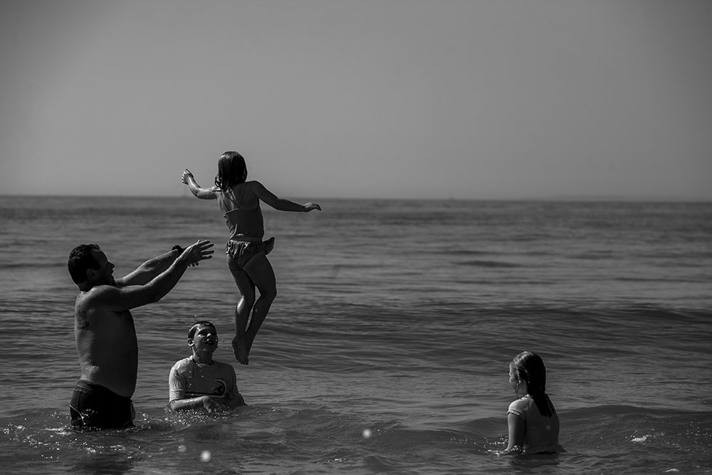 Rhode island family swims at the beach, Dad throws daughter over son in this candid beach photography.
