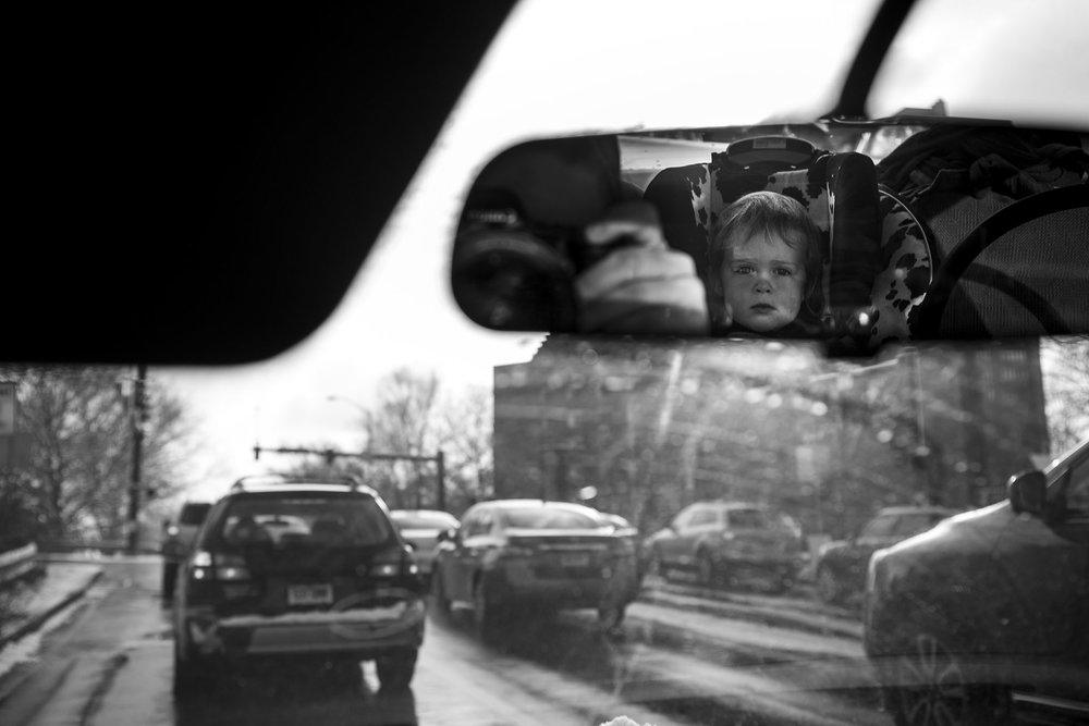 Black and white documentary family photography featuring rear view mirror with mom taking picture and toddler in car seat reflected.