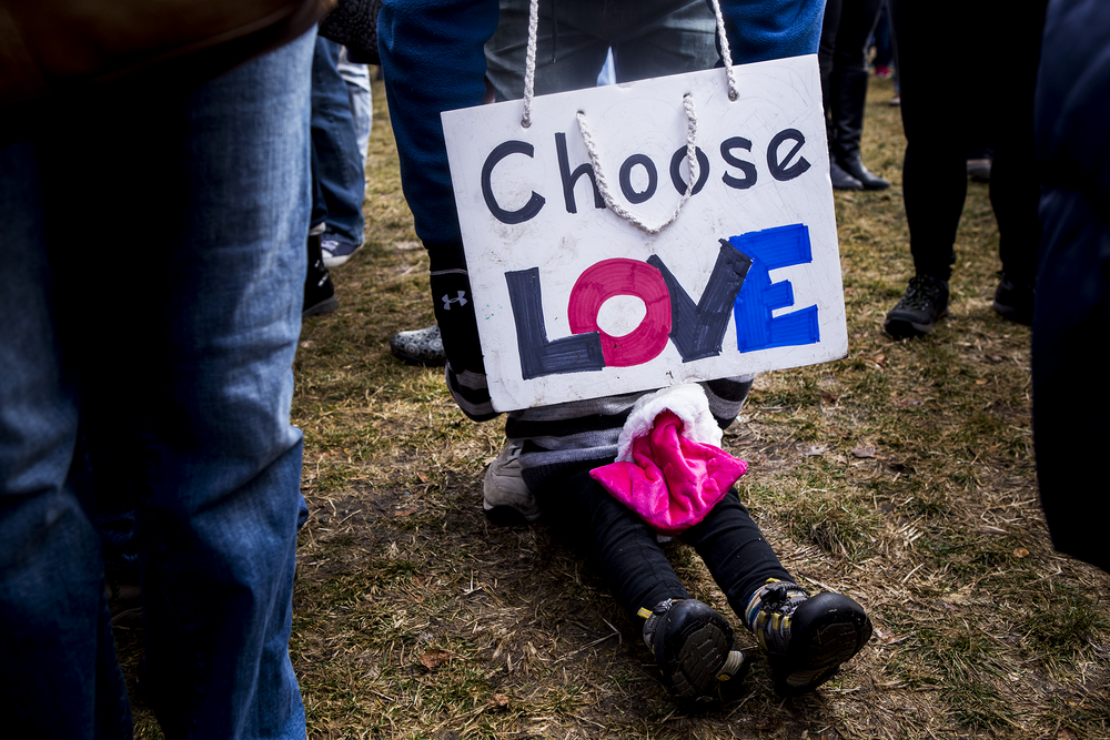 "toddler daughter sitting in a sea of legs at the women's march on washington sister march in boston, hiding behind a sign that reads ""choose love"""