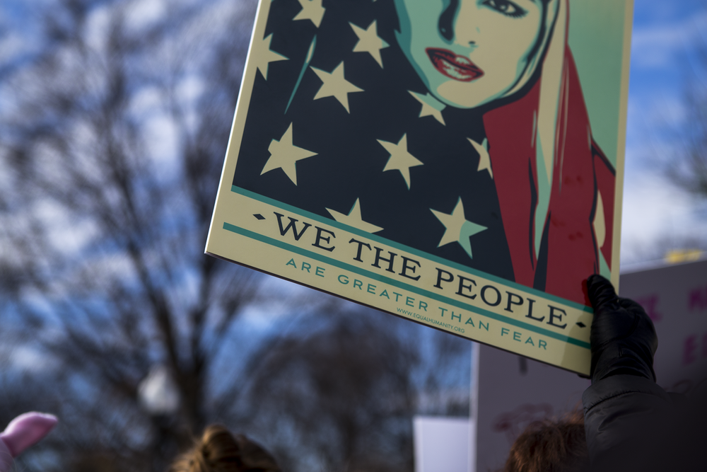"detail of shepard fairey's ""we the people"" image at the women's march on washington sister march in boston."