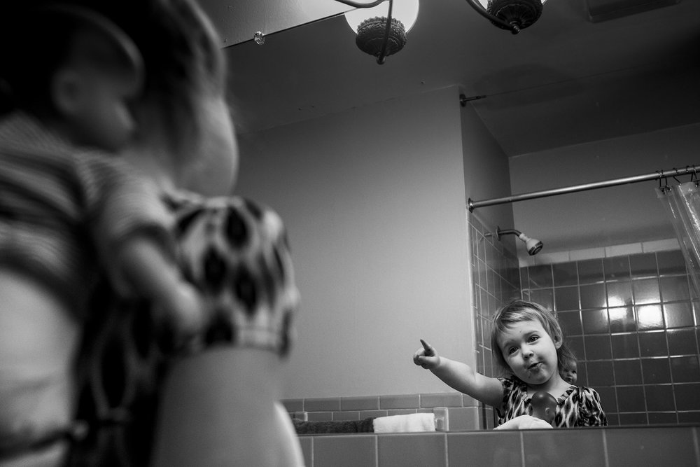 black and white portrait of child pointing at herself in bathroom mirror while babywearing her dolls.