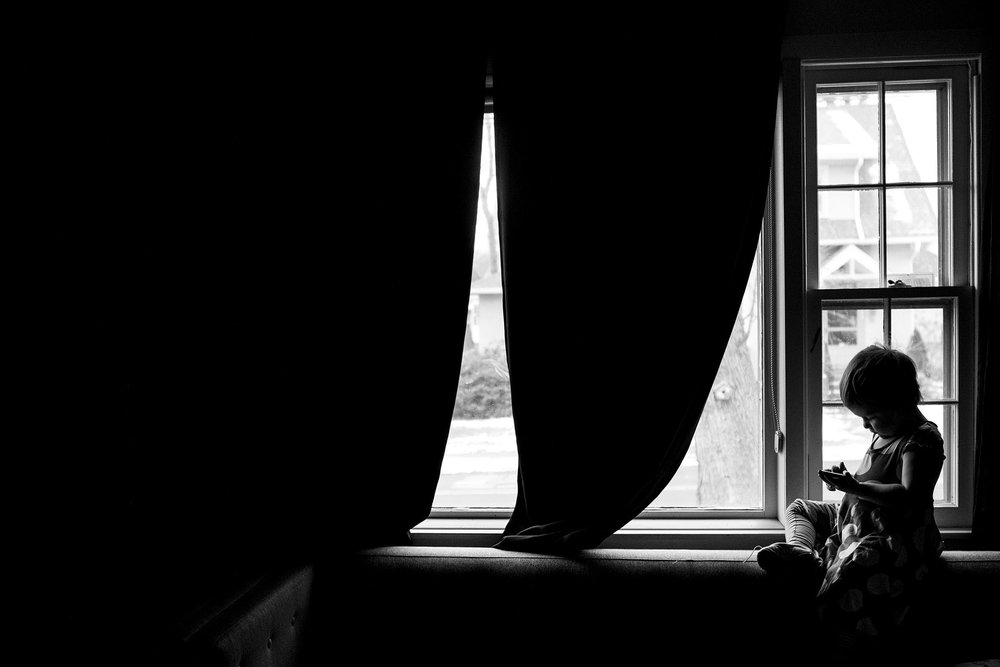 Child sits in window, black and white silhouette portrait by ct photographer chelsea silbereis.
