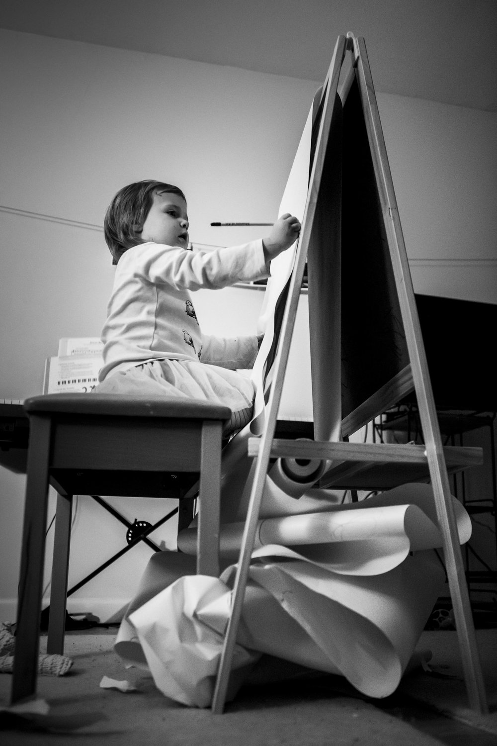 Authentic Connecticut family photographer, Chelsea Silbereis, portrait of toddler drawing with an easel and a mess of paper, Do Art.