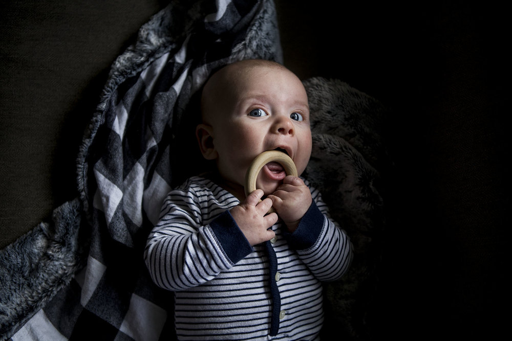 Authentic connecticut baby portraiture of baby chewing wooden teething ring, baby is 3 months old.