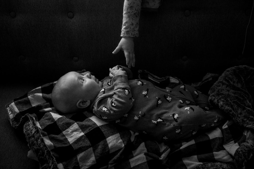 Ct siblings in black and white portrait, toddler hand reaches down towards infant brother in dramatic light.