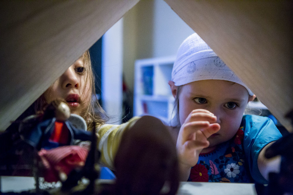 two little girl friends play with a dollhouse in this candid photograph and example of family photojournalism in CT.