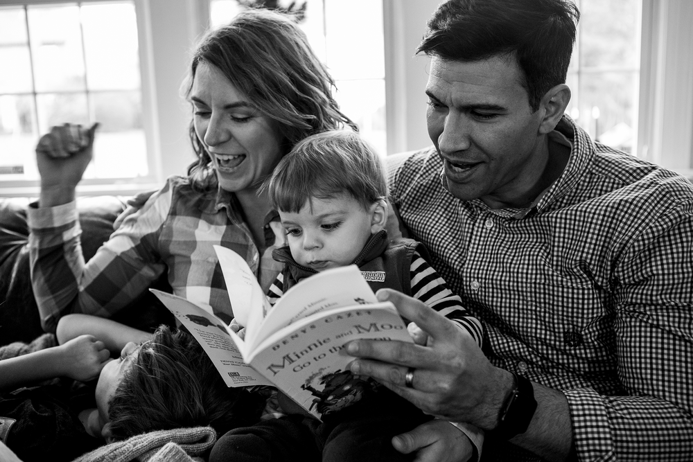 Candid black and white family photography featuring family of four reading a story and laughing.