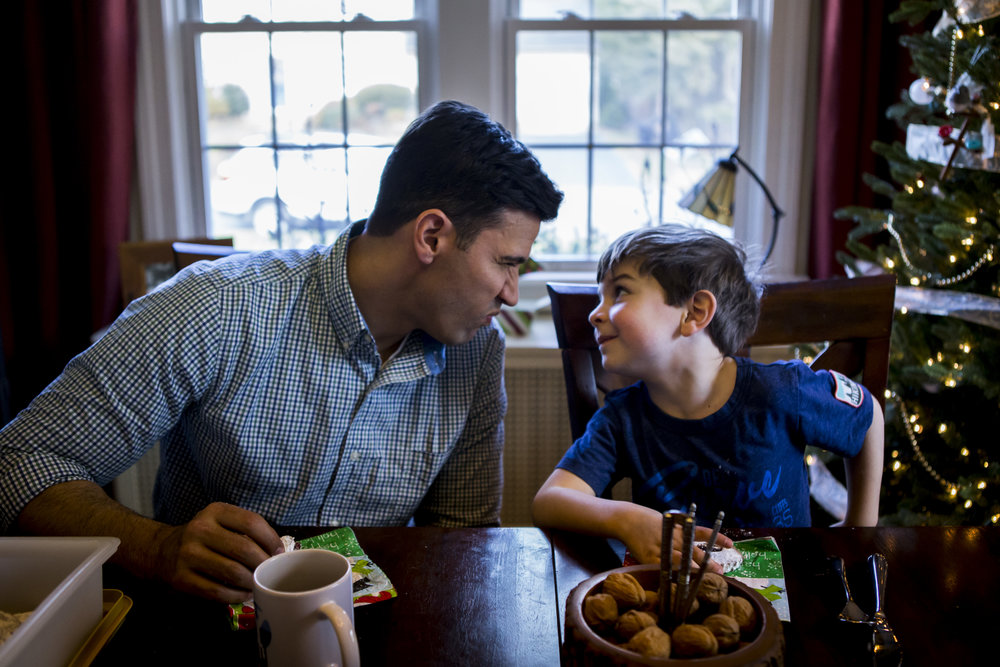 Father and son share a moment at the dinner table in this candid family photo by Connecticut day in the life photographer Chelsea Silbereis.