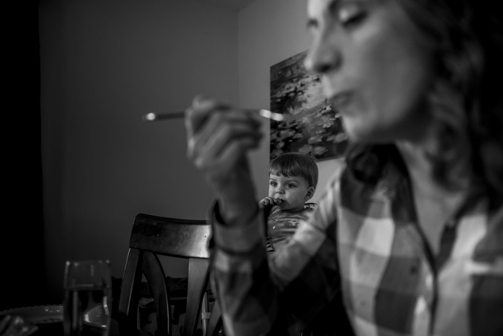 Mother and son eat dinner in this black and white family portrait