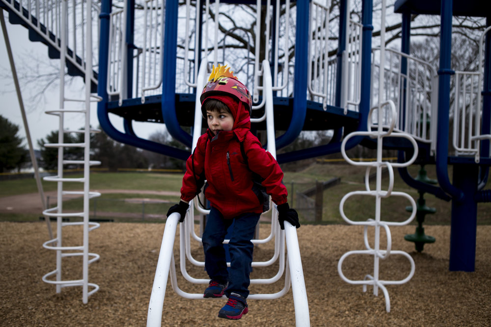 Candid environmental portrait of a child dressed in red, wearing a helmut climbing playground equipment by Connecticut child photographer specializing in authentic child portraiture.