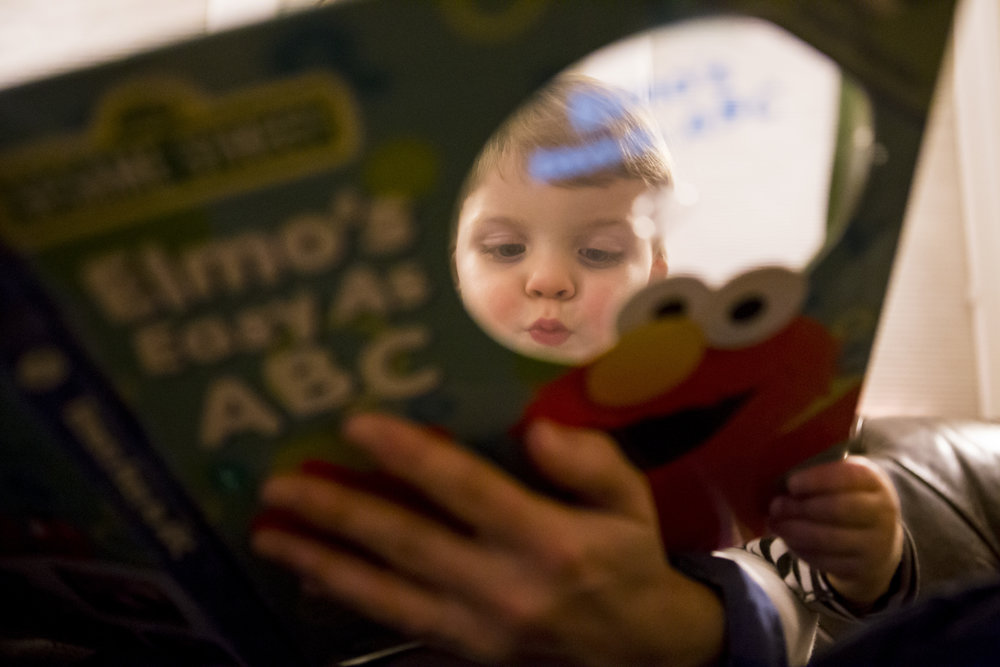 Unique family photography featuring peek-a-boo composition of toddler reading elm's abcs.