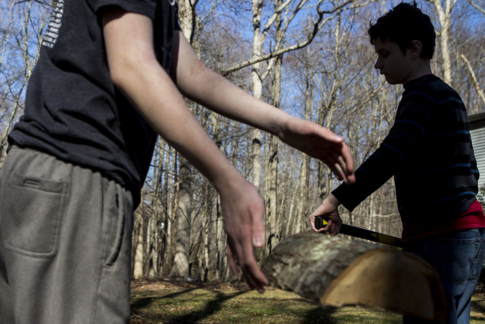 layered family photojournalism of twin boys chopping wood in the forest in Connecticut.