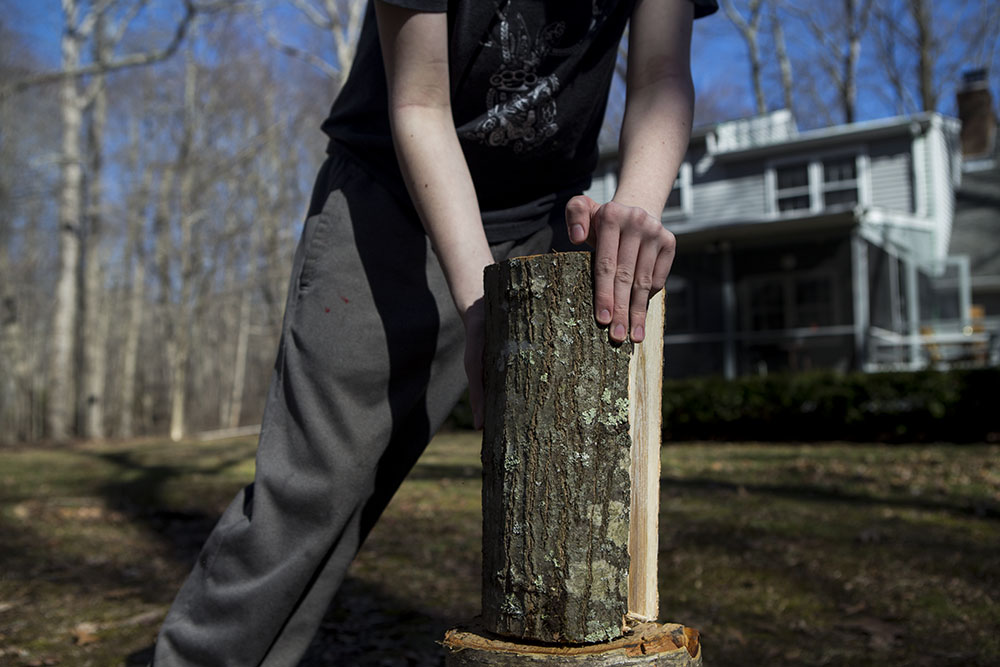 Family photojournalism, documentary family photography featuring teen lining up piece of wood for chopping.