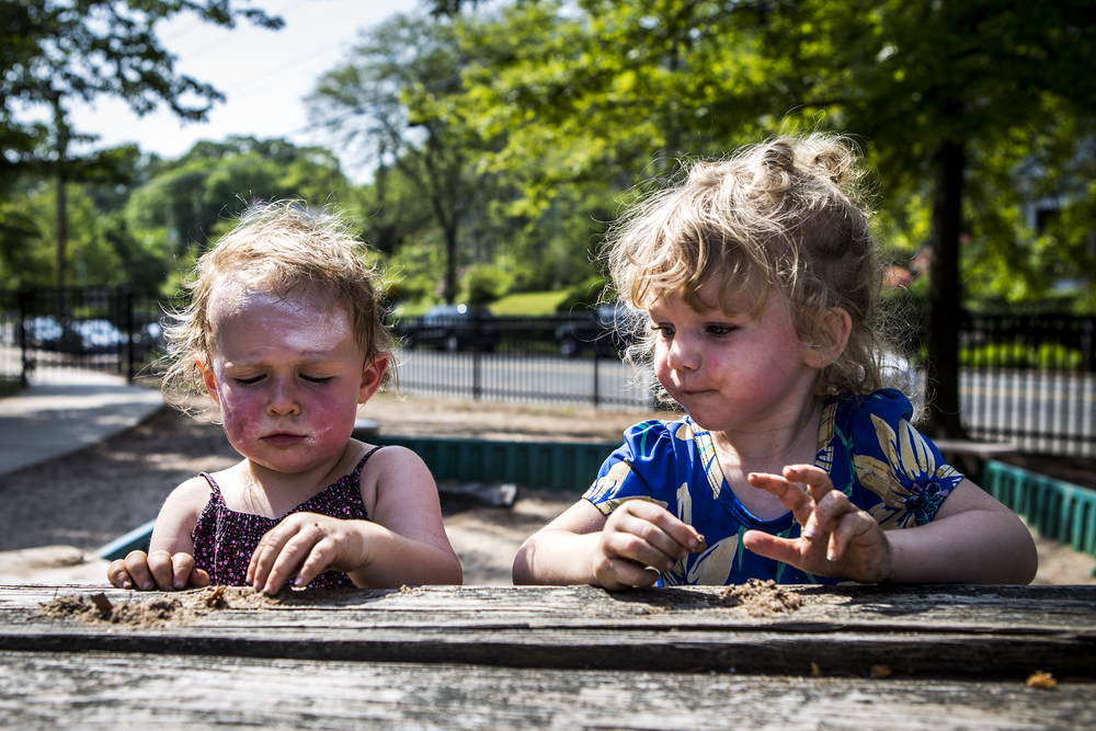 child photography in CT of two girls playing at a picnic table with lots of sunscreen and dirt on them.
