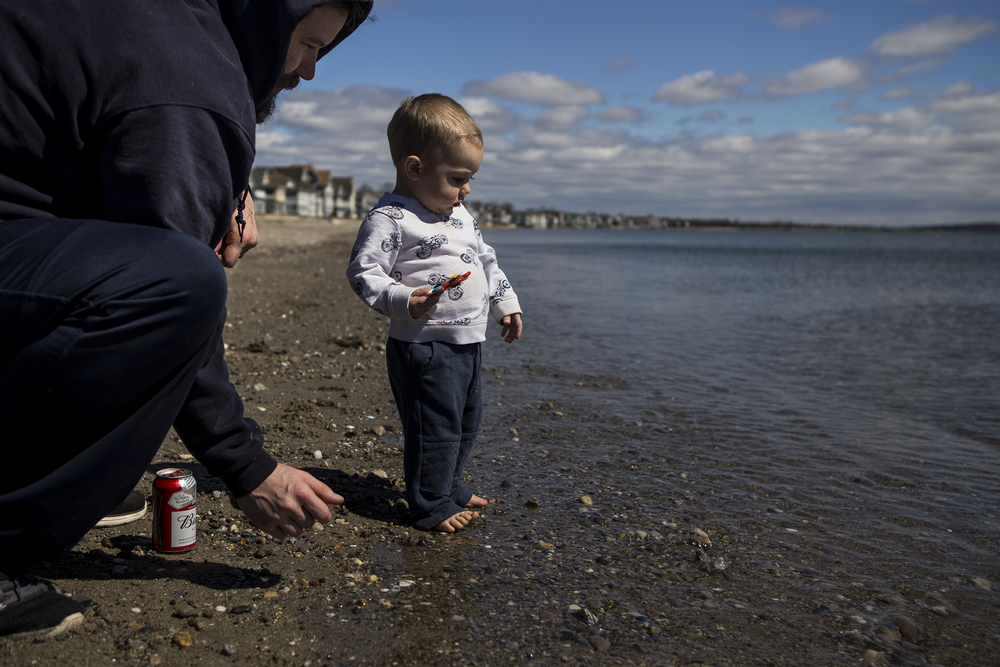 CT beach photographer features father and son throwing rocks into the ocean drinking a budweiser.
