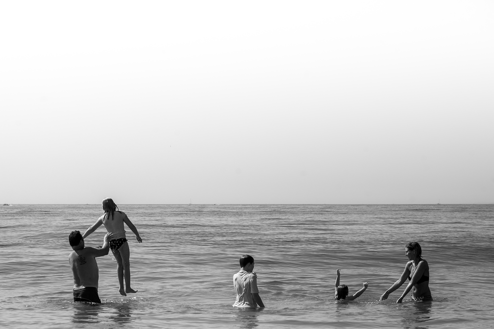 Beach family photography in ct, alternative authentic family portrait of the whole family swimming in the ocean.