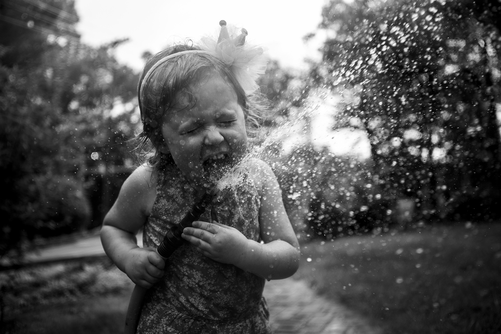 Best candid family photography in Connecticut by Chelsea Silbereis featuring black and white image of girl drinking from hose with exciting spray of water.