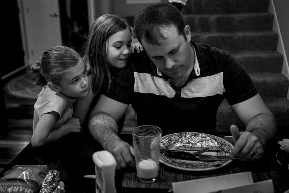Father with scheming daughters at dinnertime