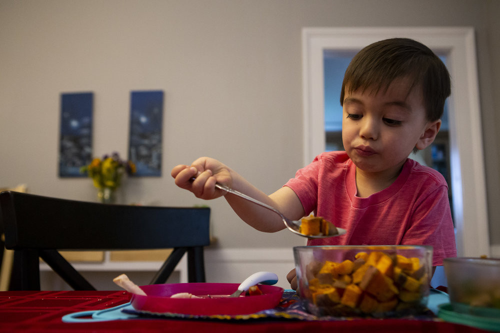 Disgruntled-looking three-year-old scoops up a spoonful of veggies
