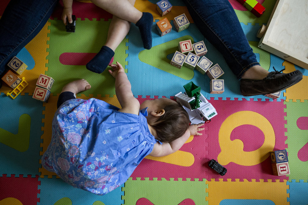 Real life family picture of boston mom and kids on the floor playing with blocks
