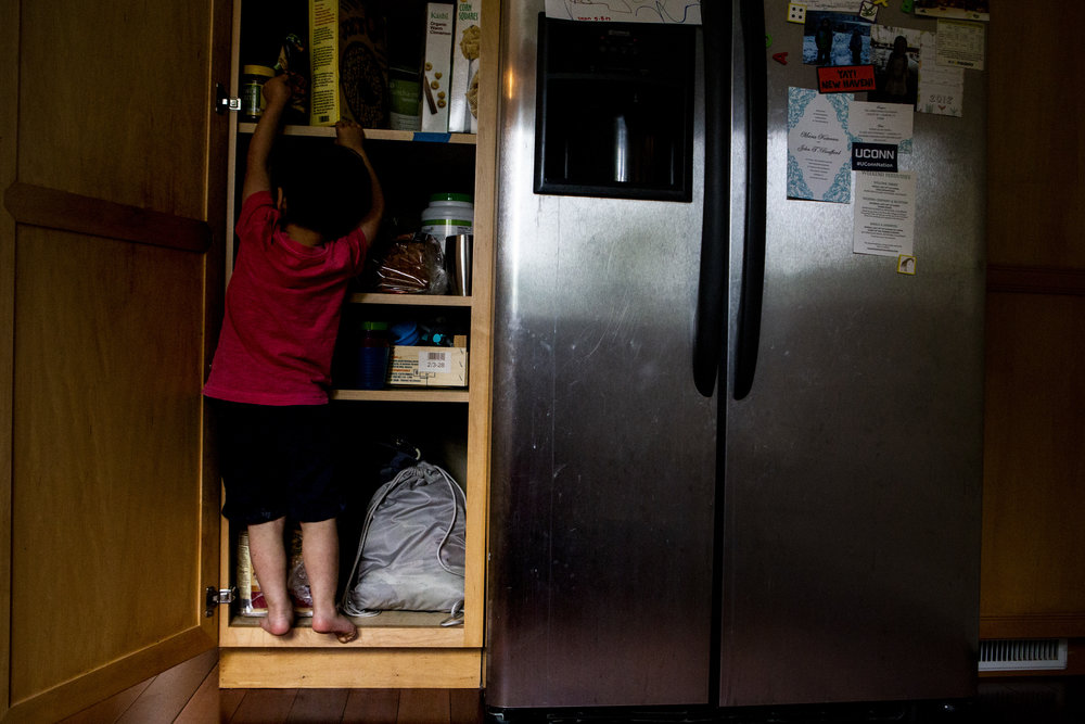 Picky-boston kid climbs into the cupboard to find some cereal