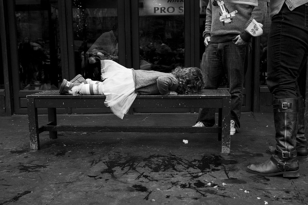 black and white family photo of boston kid passed out on a dirty bench with parents standing over her