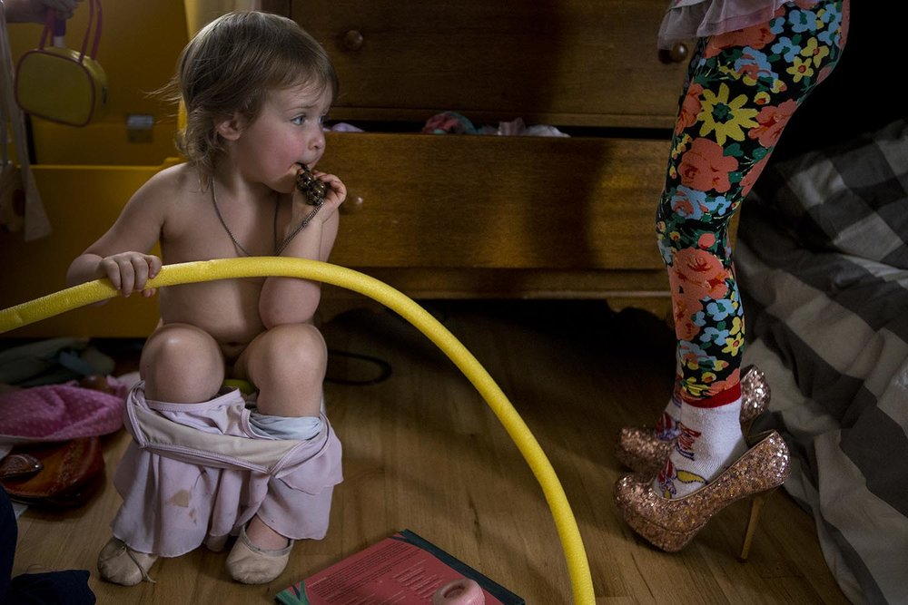 colorful and funny photograph of boston kid potty training next to older kid wearing mom's sequin high heels