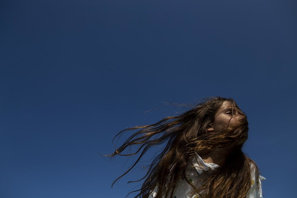 Portrait of Belmont ma kid with her hair blowing in the wind against a bright blue sky.