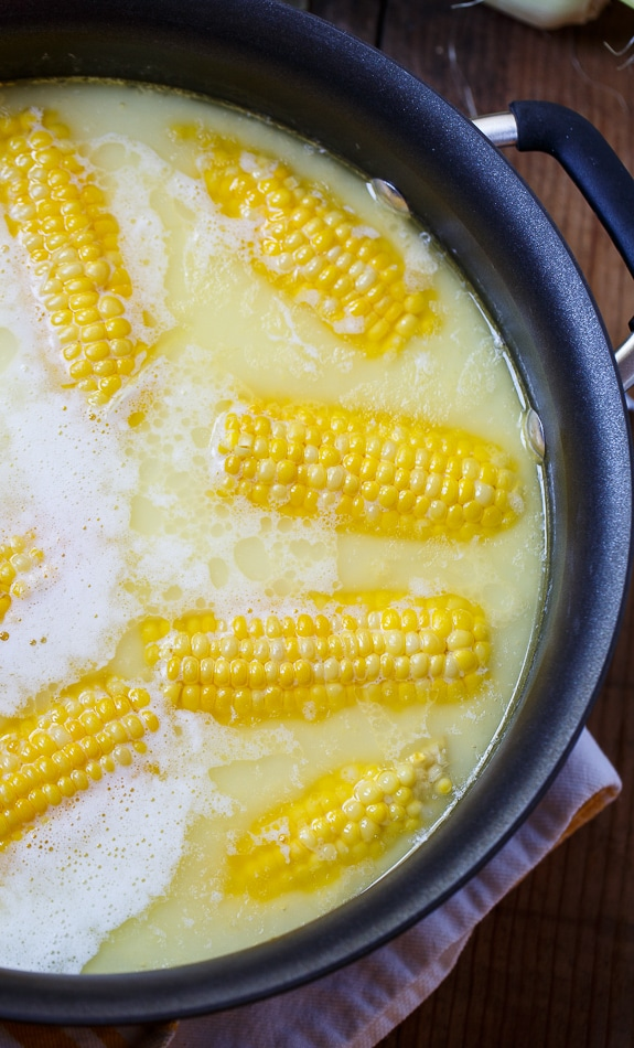 Cook corn in water with a touch of cream and butter to add riches and bring out the sweetness in the corn