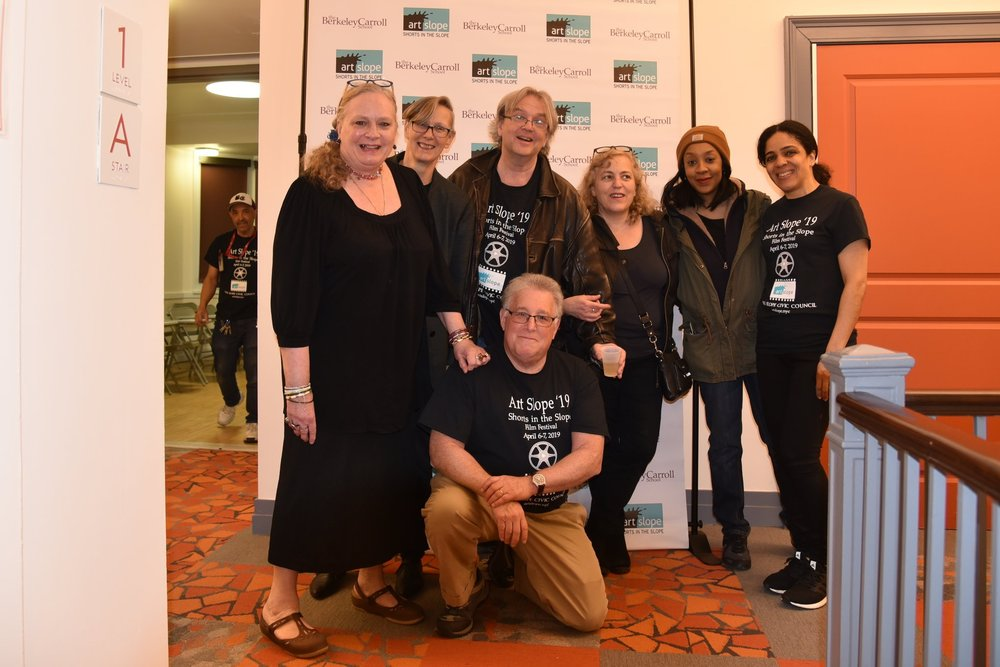 The Art Slope '19 'Shorts in the Slope' Committee (L to R): Jeanette Lee, Regi Mueller, Bill Curry, Ron Weiss (kneeling), Lee Boyes, Time Darden, Linda Wilson (not pictured: Donna Epstein and Peppy). Robinson Tejeda of Berkeley Carroll School in the background.