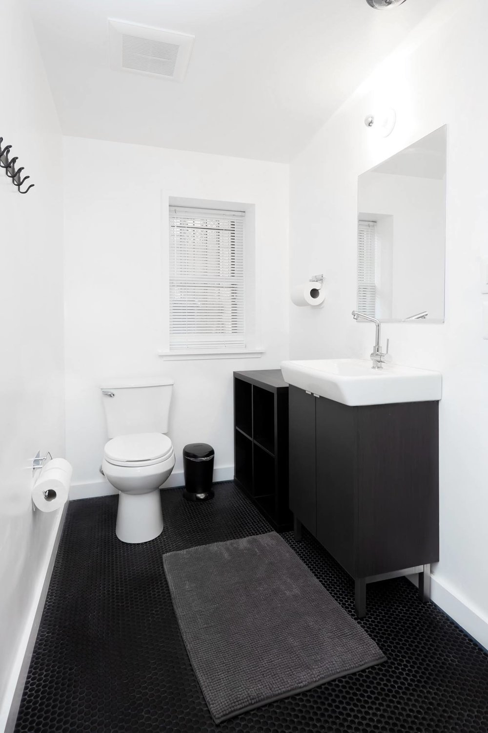 Example guest bathroom showing sink, bath mat, and toilet