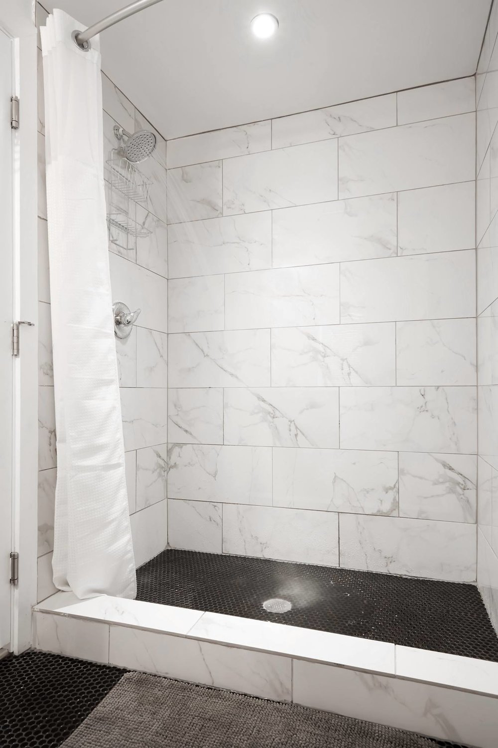 Example guest bathroom shower showing marble-looking tile, chrome showerhead