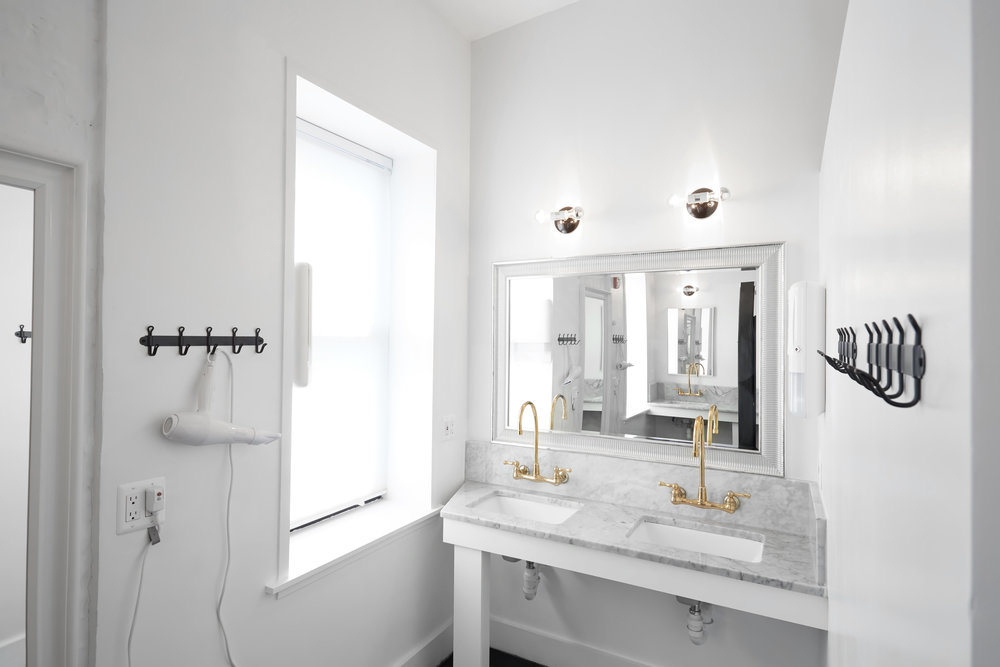 Example guest bathroom showing marble countertop, brass faucets, bright window