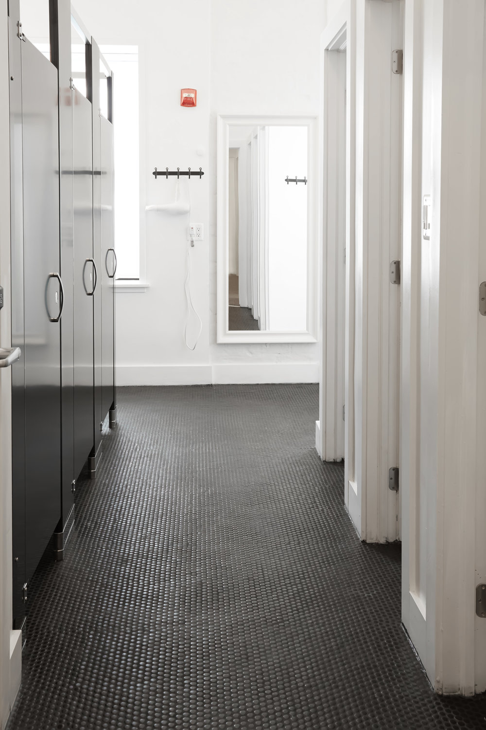 Example guest bathroom shower stalls and clean black penny tile floor