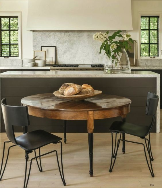 I'm incredibly inspired by this kitchen, designed by Betsy Brown. It's handsome yet elegant, and so casually livable. Often times in a kitchen, the hood is the focal point that's cladded in some sort of outstanding material. But here while still a focal point, the hood is quiet and addressed with a simple, matte stucco finish. The marble countertops are classic in form, but have been fabricated in a contemporary fashion by extending to the floor. The painted cabinets are handsome in color, perfectly offsetting the antique round table and modern klismos chairs by Donghia. I also love the tone-on-tone paint for this space, because it's a lovely backdrop for the dark windows.