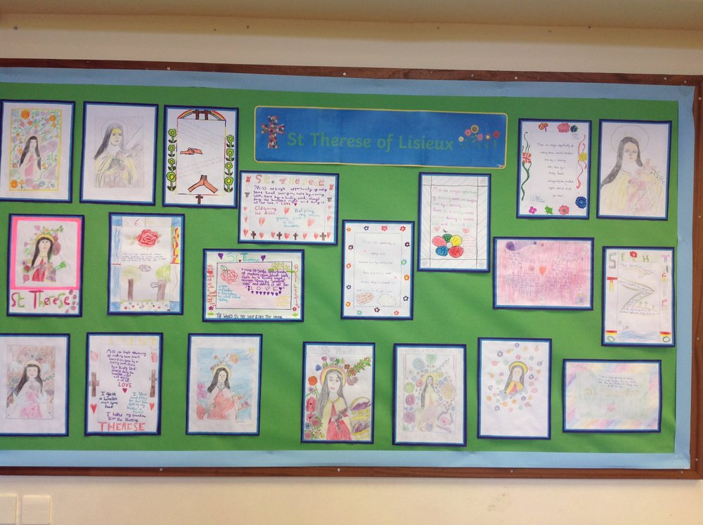 This photograph shows our art work and famous quotes of our class saint and how we follow in her footsteps today: 'When people walk past me in school I greet them with a friendly hello' 'I like to help my Grandma with the shopping at the weekend'