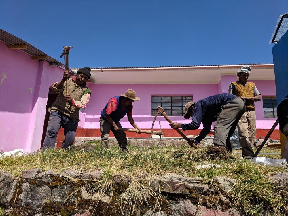 Community volunteers dig a foundation