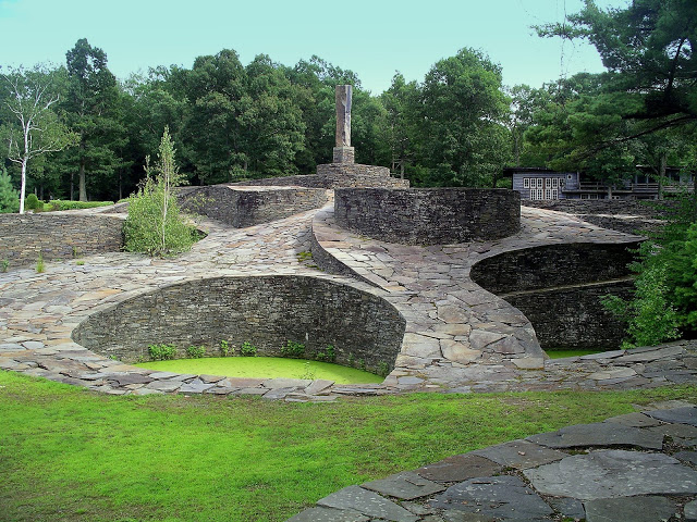 Destination: Opus 40 is a large environmental sculpture in Saugerties, New York, created by sculptor and quarryman Harvey Fite. It comprises a sprawling series of dry-stone ramps, pedestals and platforms covering 6.5 acres of a bluestone quarry.