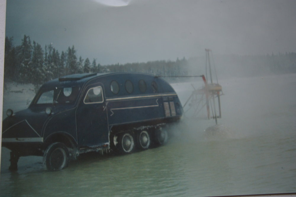 "Bombadier with an 18"" auger flooding the frozen lake with lake water to build winter ice roads in Northern Manitoba"