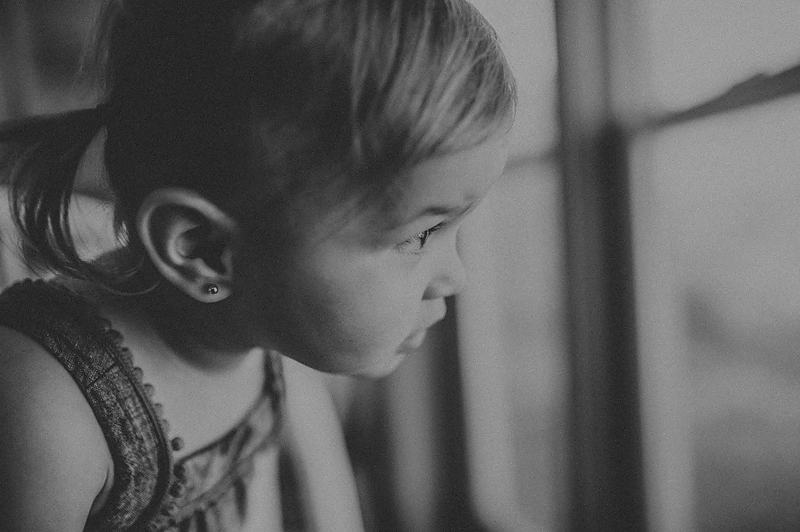Baby girl with pigtails looking out window