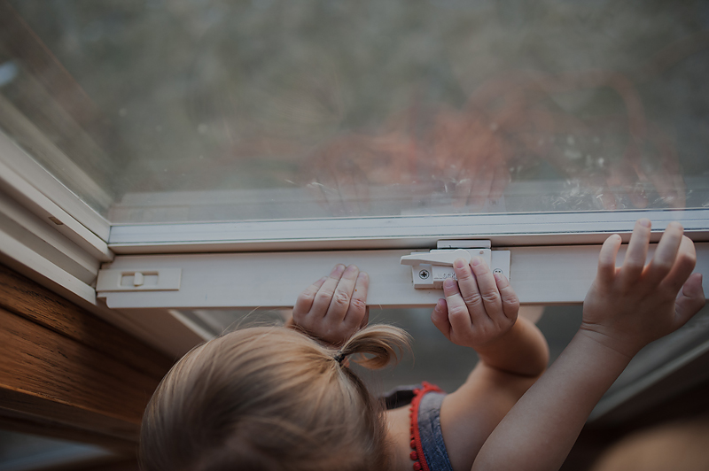 Baby girl with pigtails and big brother with fingers on windowsill