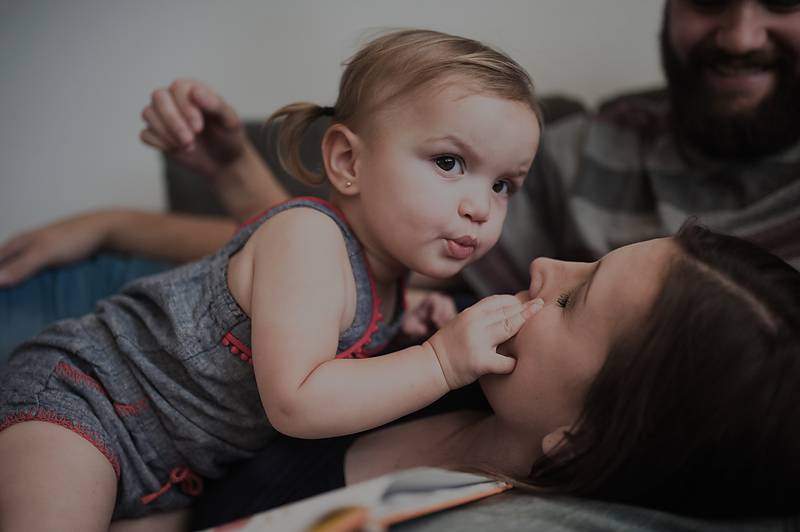 Baby girl grabbing moms face making kissy lips