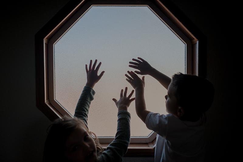 Little kids hands playing in window