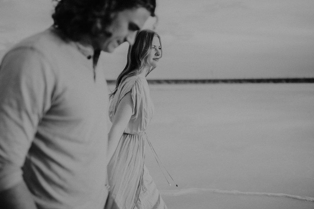 Couple holding hands walking on salt flats