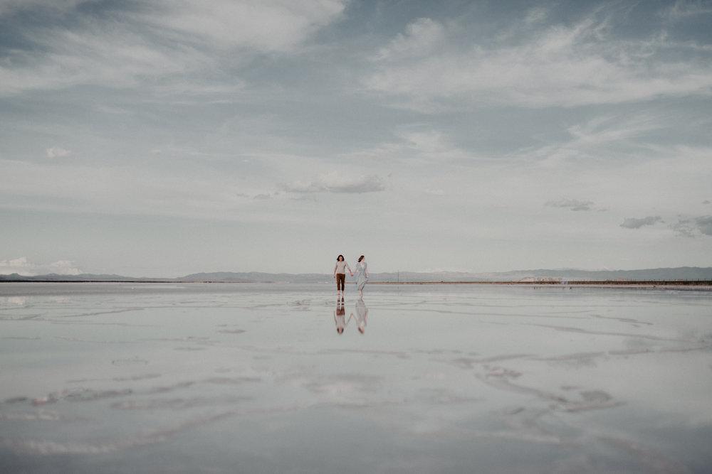 Couple standing on salt flats holding hands