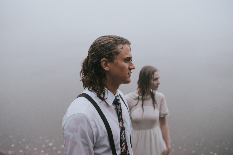 Couple in front of foggy lake in rain