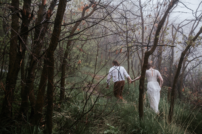 Couple running through trees in rain