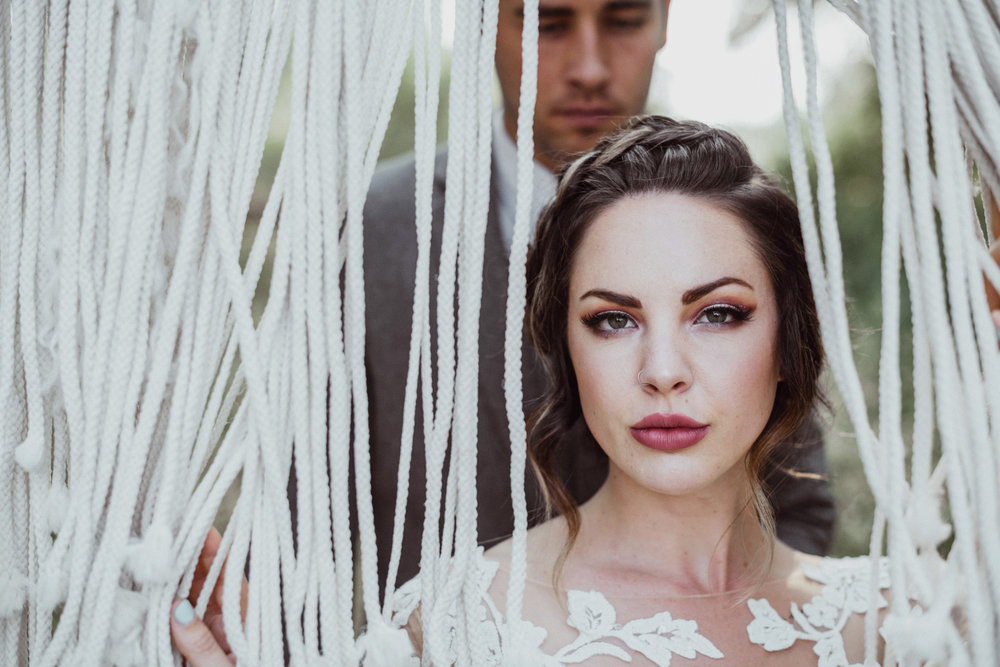 Bride and groom in front of boho Macrame